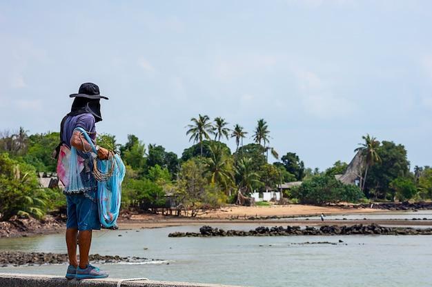 Uomo che tiene le reti da pesca sfondo mare e cielo. Foto Premium