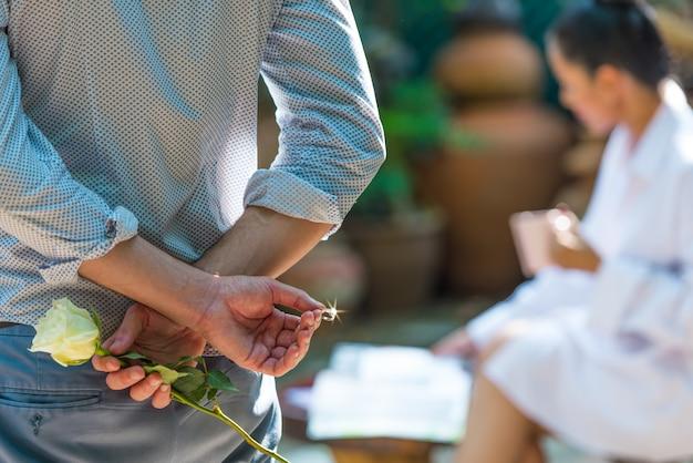Uomo che tiene rosa bianca e fede dietro la schiena per fare una proposta di matrimonio. Foto Premium