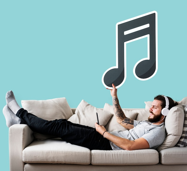 Uomo che tiene un'icona su un divano Foto Gratuite
