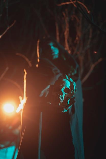 Uomo che tiene una lanterna e un teschio nella notte Foto Gratuite