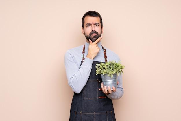 Uomo che tiene una pianta sopra il pensiero isolato Foto Premium