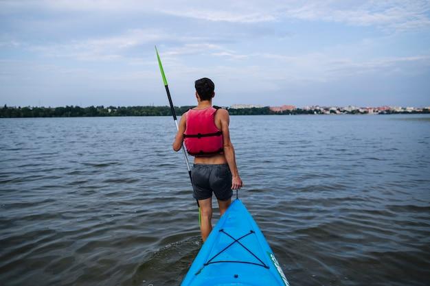 Uomo che trasporta kayak blu nel lago idilliaco Foto Gratuite