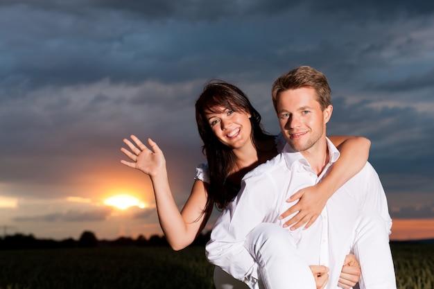 Uomo che trasporta la sua donna sulle spalle con il tramonto sullo sfondo Foto Premium