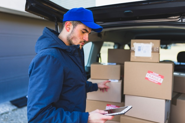 Uomo che usa la tavoletta e consegna scatole Foto Gratuite