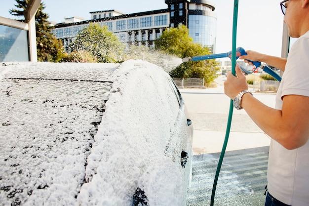 Uomo che usando un tubo per pulire la sua auto Foto Gratuite