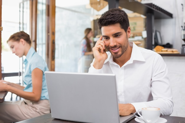 Uomo che utilizza computer portatile e telefono cellulare nella caffetteria Foto Premium