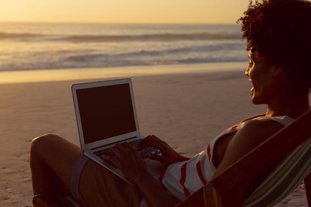 Uomo che utilizza computer portatile mentre ci si rilassa in una sedia di spiaggia sulla spiaggia Foto Gratuite