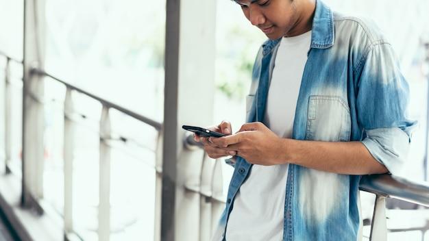 Uomo che utilizza smartphone, durante il tempo libero. il concetto di usare il telefono è essenziale nella vita di tutti i giorni. Foto Premium
