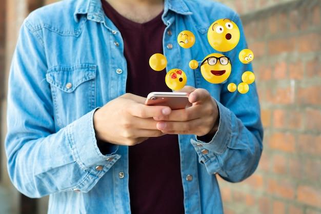 Uomo che utilizza smartphone per inviare emoji Foto Premium