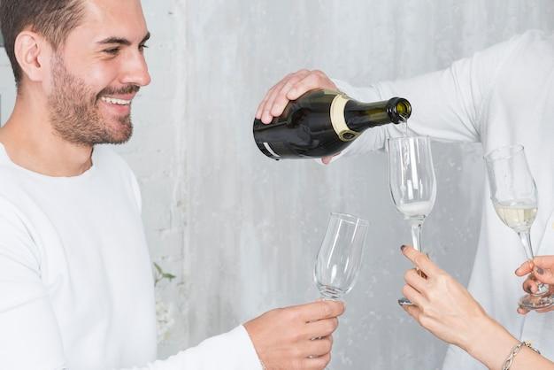 Uomo che versa champagne in bicchieri in festa Foto Gratuite
