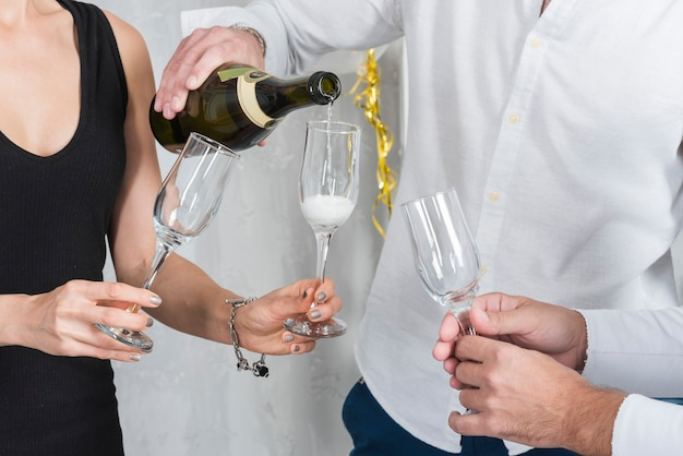 Uomo che versa champagne nei bicchieri Foto Gratuite