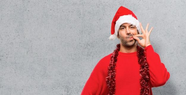 Uomo con abiti rossi che celebrano le vacanze di natale mostrando un segno di chiusura della bocca Foto Premium