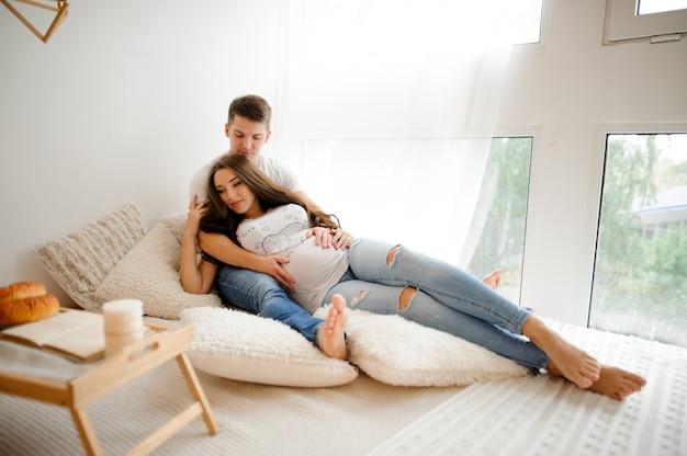 Uomo con bella donna incinta che si trova sul letto in una stanza bianca Foto Premium