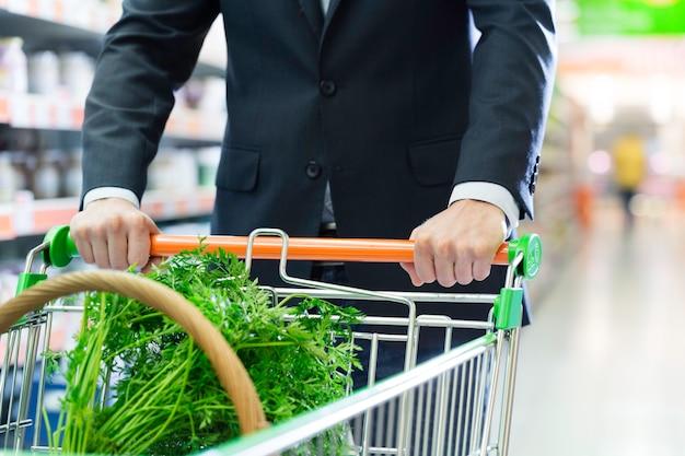 Uomo con carrello della spesa in un supermercato Foto Premium