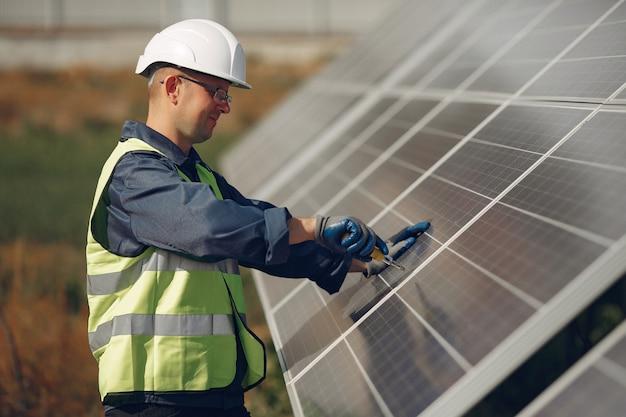 Uomo con casco bianco vicino a un pannello solare Foto Gratuite