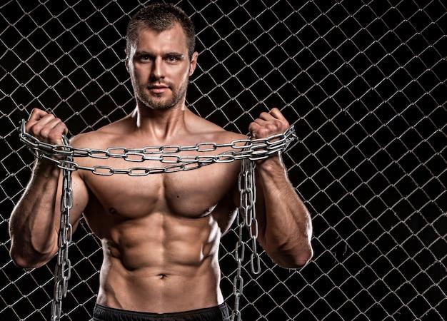 Uomo con catene su una recinzione Foto Gratuite