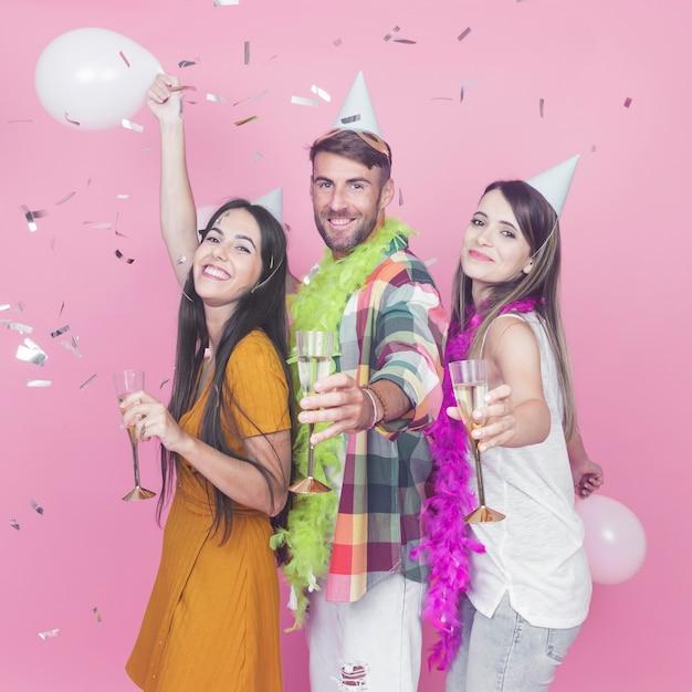 Uomo con due amici femminili godendo la festa su sfondo rosa Foto Gratuite