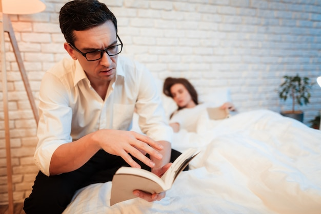 Uomo con gli occhiali concentrato sul libro di lettura. Foto Premium