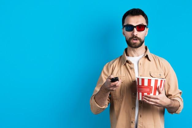 Uomo con gli occhiali di film che indica telecomando Foto Gratuite