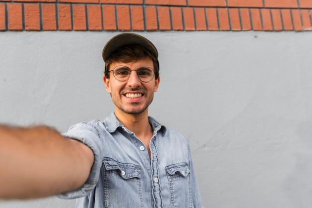 Uomo con gli occhiali prendendo un selfie Foto Gratuite