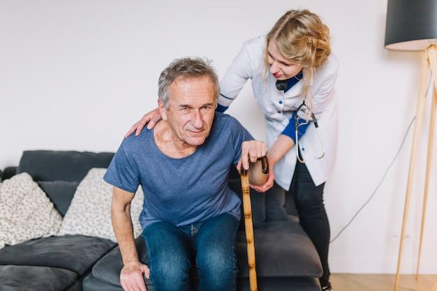 Uomo con il bastone nella casa di riposo Foto Gratuite