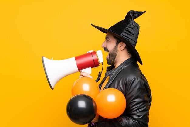 Uomo con il cappello della strega che tiene gli aerostati di aria neri e arancioni per la festa di halloween che grida tramite un megafono Foto Premium
