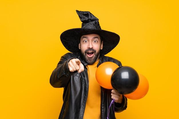 Uomo con il cappello della strega che tiene gli aerostati di aria neri e arancioni per la festa di halloween sorpresa e che indica parte anteriore Foto Premium