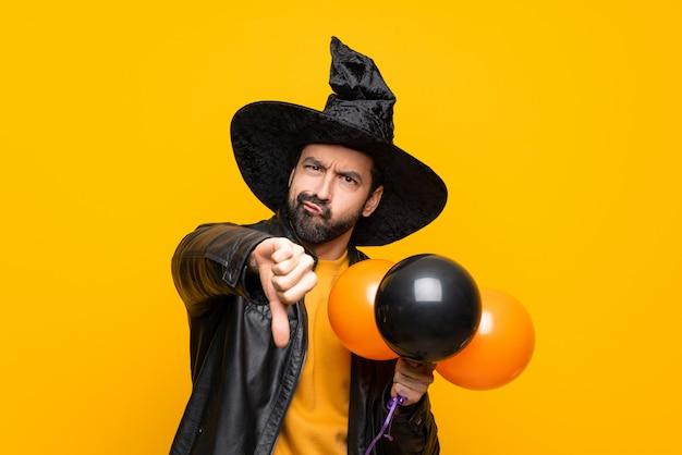 Uomo con il cappello della strega che tiene gli aerostati di aria neri ed arancioni per il partito di halloween che mostra pollice giù con l'espressione negativa Foto Premium
