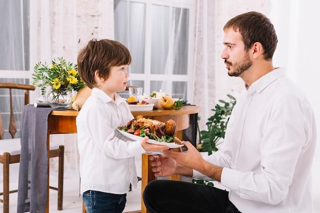 Uomo con il figlio che tiene pollo al forno sul piatto Foto Gratuite