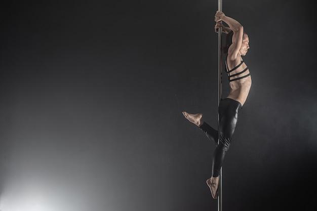 Uomo con il pilone ballerino del palo maschile danza su uno sfondo nero Foto Premium