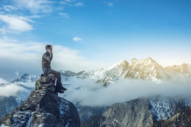 Uomo con il telefono in mano sulla cima di una montagna innevata Foto Premium