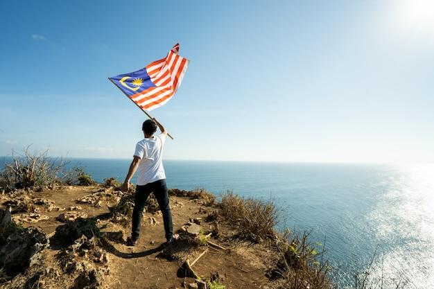 Uomo con la bandiera indonesiana dell'indonesia in cima alla montagna Foto Premium