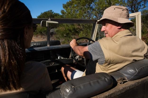 Uomo con la donna che osserva via mentre si guida il veicolo Foto Gratuite