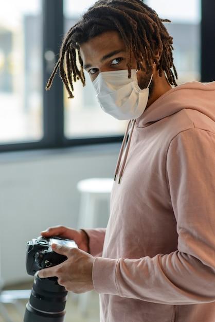 Uomo con la maschera che tiene la fotocamera Foto Gratuite