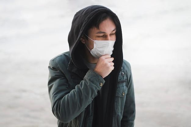 Uomo con la mascherina medica che propone all'esterno Foto Gratuite