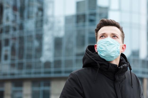 Uomo con la mascherina medica che propone nella città con lo spazio della copia Foto Gratuite