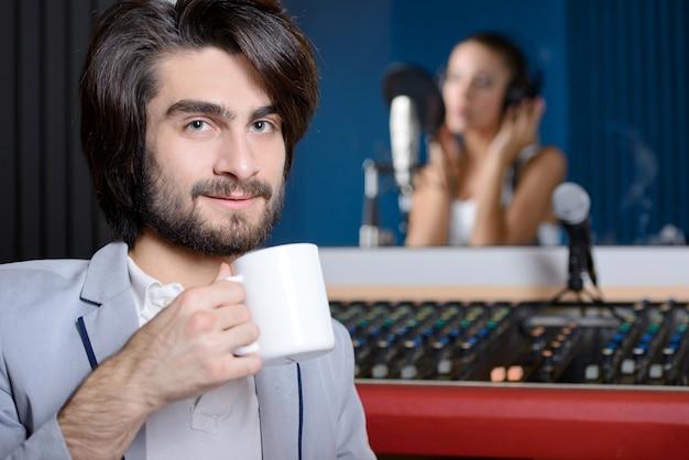 Uomo con la tazza di caffè in studio di registrazione, ragazza vaga che canta Foto Premium