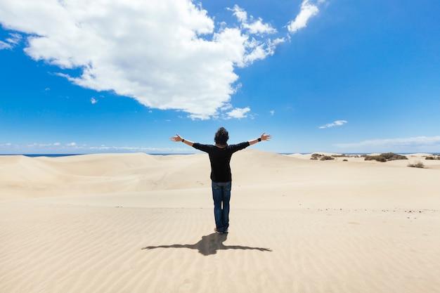 Uomo con le braccia spalancate su un paesaggio di dune del deserto. concetto di viaggi e vacanze. Foto Premium