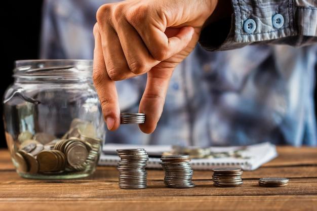 Uomo con le monete di risparmio sul barattolo Foto Gratuite