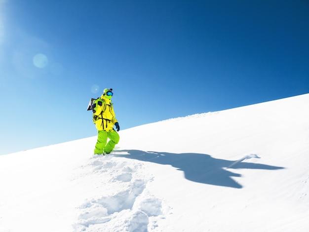 Uomo con lo snowboard che resta nella neve al fondo del cielo Foto Premium