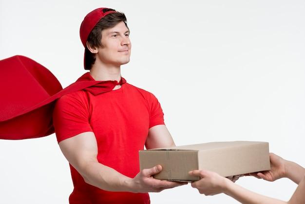 Uomo con mantello consegna scatola Foto Gratuite