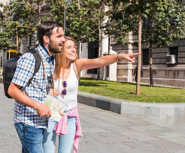 Uomo con mappa guardando donna felice che punta verso qualcosa Foto Gratuite