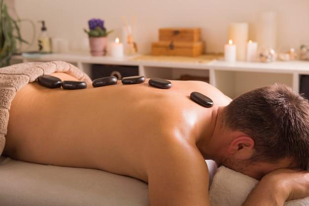 Uomo con pietre sul lettino da massaggio presso spa con trattamento del corpo. persona sdraiata e rilassante durante il