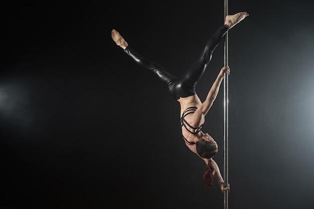 Uomo con pilone. ballerino maschio del palo che balla su un fondo nero Foto Premium