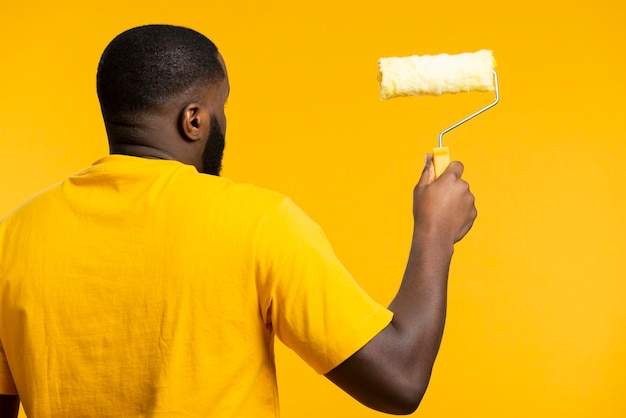 Uomo con rotolo di pittura Foto Gratuite