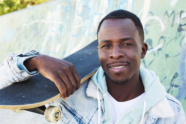 Uomo con skateboard in ambiente urbano Foto Gratuite