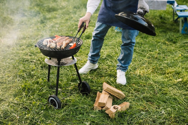 Uomo con un barbecue in natura Foto Gratuite