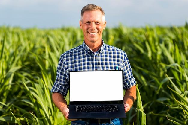 Uomo con un computer portatile in un modello del campo di mais Foto Gratuite