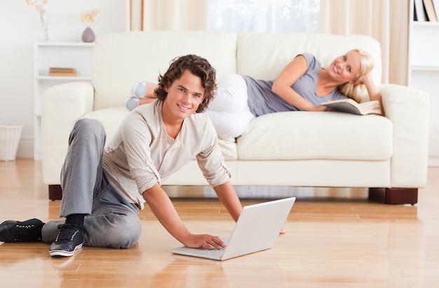 Uomo con un notebook mentre la sua ragazza è con un libro Foto Premium