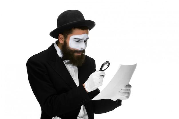 Uomo con una faccia mime lettura attraverso la lente di ingrandimento Foto Gratuite